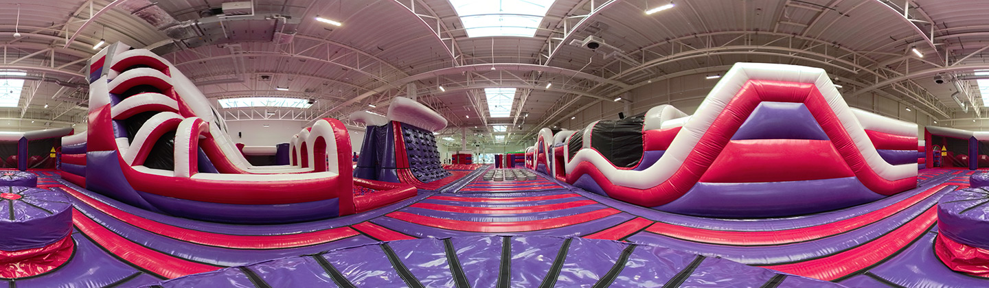 purple and red themed InflataNation inflatable theme park people jumping