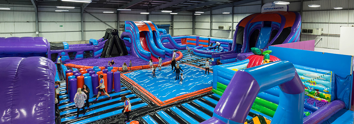 purple and blue themed InflataNation inflatable theme park people jumping
