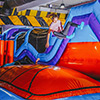 kids jumping in orange blue purple obstacle course